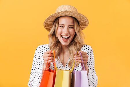 Portrait of a lovely cheerful young blonde girl wearing summer dress standing isolated over yellow background, carrying shopping bags