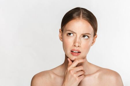 Image of serious woman touching her chin and looking upward isolated over white background