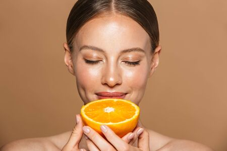 Image of a beautiful pleased young amazing woman posing isolated over brown chocolate background wall holding orange.