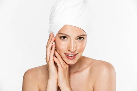 Image of seductive woman wrapped in towel posing after shower with hands at face isolated over white background Stock fotó