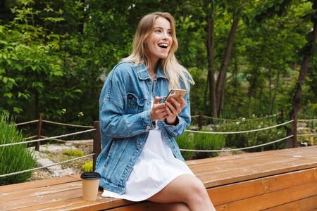 Image of amazing shocked excited young woman student posing outdoors in park using mobile phone. Imagens