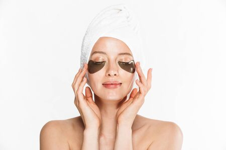 Image of relaxed woman wrapped in towel applying cosmetic eye patches isolated over white background Фото со стока
