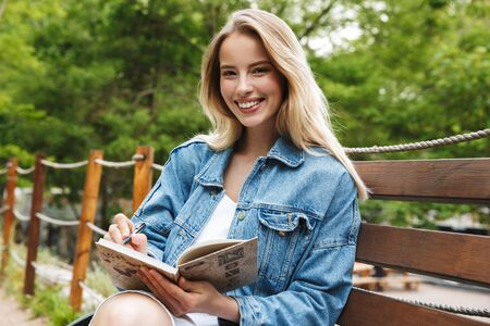 Image of amazing happy young woman student posing outdoors in park writing notes in notebook.