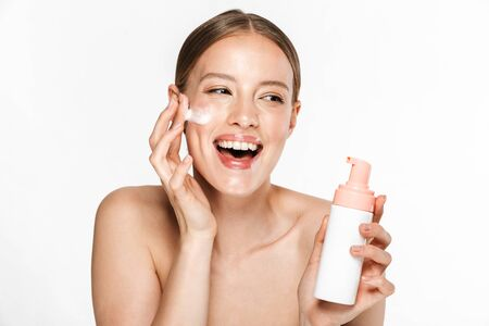 Image of beautiful half-naked woman rejoicing while washing her face with foaming facial cleanser isolated over beige background Stockfoto