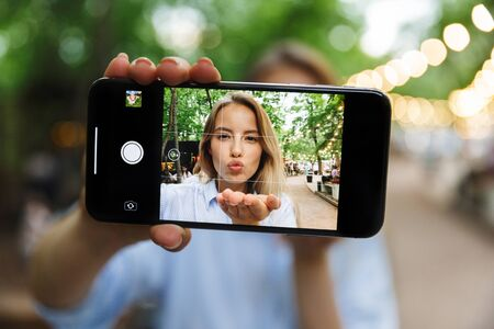Image of amazing excited happy young woman posing outdoors in park take a selfie by mobile phone. Imagens