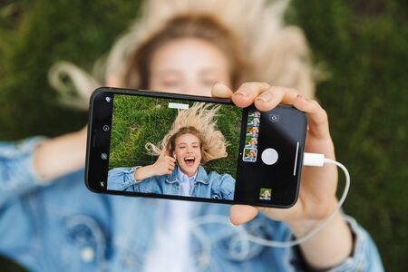 Image of amazing excited happy young woman posing outdoors in park using mobile phone listening music with earphones lies on grass take a selfie.