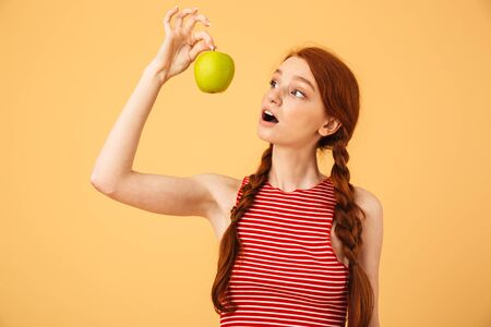 Image of a shocked young beautiful redhead woman posing isolated over yellow background holding apple.