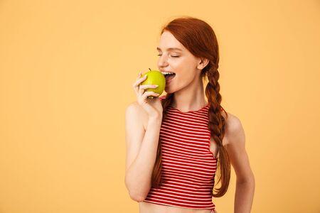 L'immagine di una giovane bella donna rossa felice in posa isolata su sfondo giallo mangia mela.