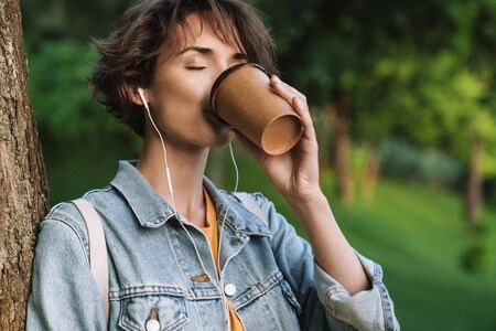 Attractive cheerful young girl wearing casual outfit spending time outdoors at the park, listening to music with earphones, holding takeaway coffee cup