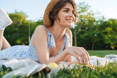 Image of a beautiful happy young pretty woman lies on grass in park outdoors reading book.