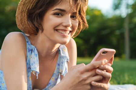 Image of a beautiful happy young pretty woman in green park outdoors using mobile phone.