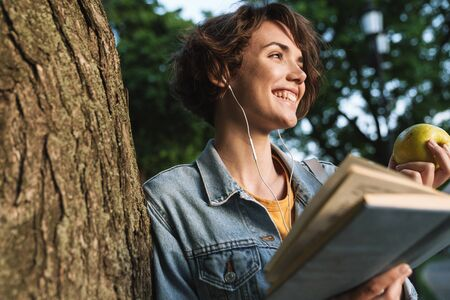 Attractive smiling young girl wearing casual outfit spending time outdoors at the park, leaning on a tree, eating green apple while reading a book Stock Photo - 128777249