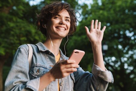 Attractive young girl wearing casual outfit spending time outdoors at the park, listening to music with earphones, holding mobile phone, waving hand