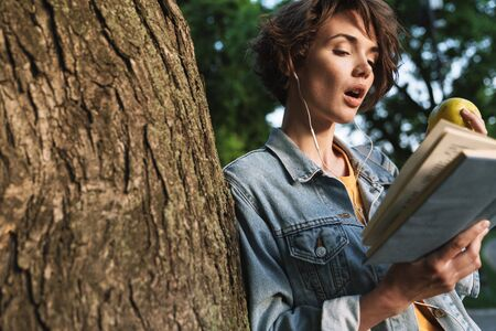 Attractive shocked young girl wearing casual outfit spending time outdoors at the park, leaning on a tree, eating green apple while reading a book