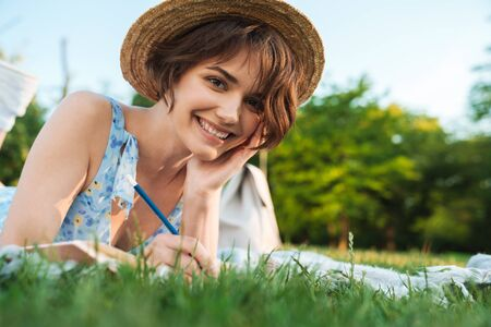 Image of a beautiful shocked young pretty woman in green park outdoors writing notes in notebook.