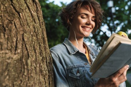 Attractive smiling young girl wearing casual outfit spending time outdoors at the park, leaning on a tree, eating green apple while reading a book Stock Photo