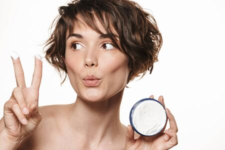 Beauty portrait of a lovely young topless woman with short brunette hair standing isolated over white background, applying face cream, showing container, showing fingers 写真素材