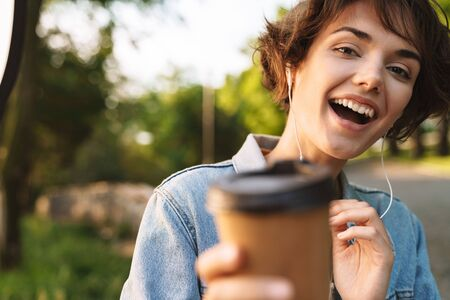 Image of excited caucasian woman 20s wearing denim jacket smiling while drinking takeaway coffee and using earphones during walk through green park