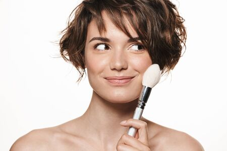 Beauty portrait of a lovely smiling young topless woman with short brunette hair standing isolated over white background, applying makeup with a brush 写真素材