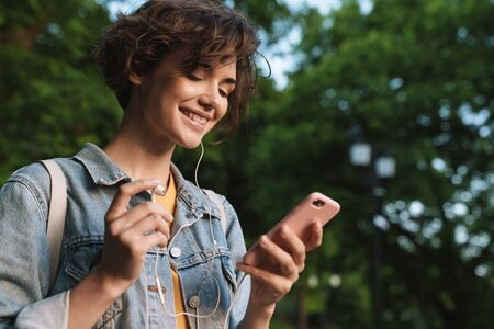 Attractive happy young girl wearing casual outfit spending time outdoors at the park, listening to music with earphones, holding mobile phone