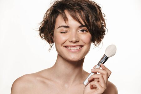 Beauty portrait of a lovely excited young topless woman with short brunette hair standing isolated over white background, applying makeup with a brush 写真素材