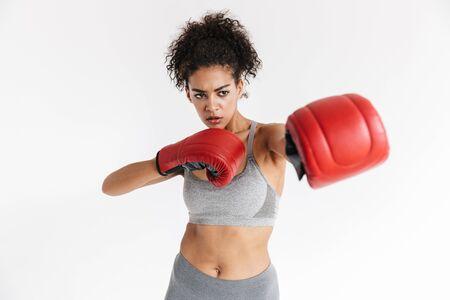 Imagen de un hermoso joven boxeador de mujer africana de fitness increíble deportes posando aislado sobre fondo blanco en guantes.