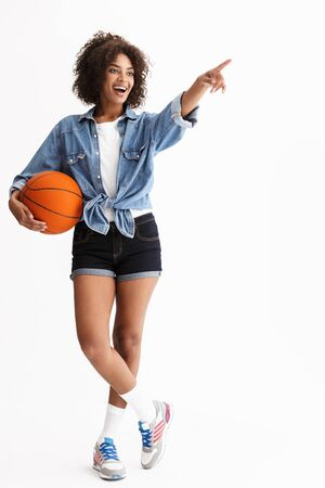Full length portrait of a young cheerful african woman wearing casual denim clothes isolated over white background, holding basketball Standard-Bild - 130055653