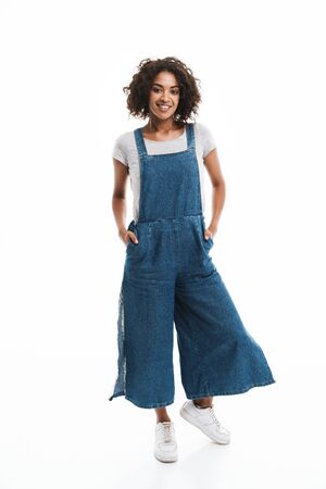 Image of happy african american woman dressed in denim overalls smiling at camera with hands in pockets isolated over white background