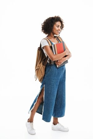 Image of lovely african american woman wearing backpack smiling and holding exercise books isolated over white background Foto de archivo