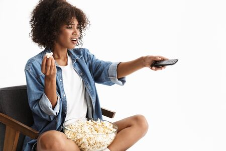 Cheerful young african woman wearing casual denim clothing sitting in a chair isolated over white background, eating popcorn while watching a movie, holding remote control Stock Photo