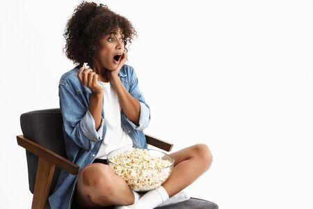 Cheerful young african woman wearing casual denim clothing sitting in a chair isolated over white background, eating popcorn while watching a movie