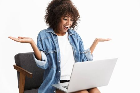 Attractive young african woman wearing denim sitting in chair isolated over white background, working on laptop computer, chatting