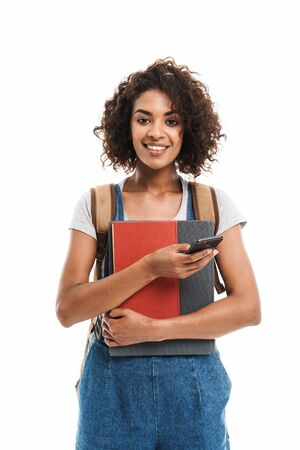 Image of pretty african american woman wearing backpack holding exercise books and cellphone isolated over white background
