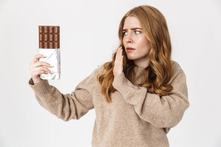 Attractive confused young girl wearing sweater standing isolated over white background, holding chocolate bar Stockfoto