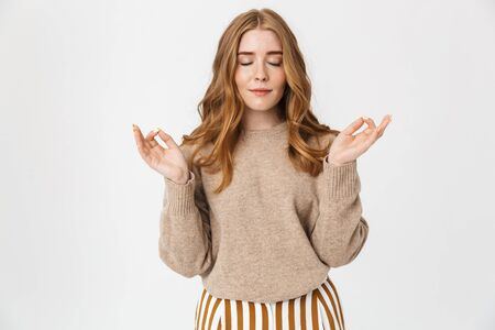 Beautiful young girl with long blond curly hair wearing sweater standing isolated over white background, meditating