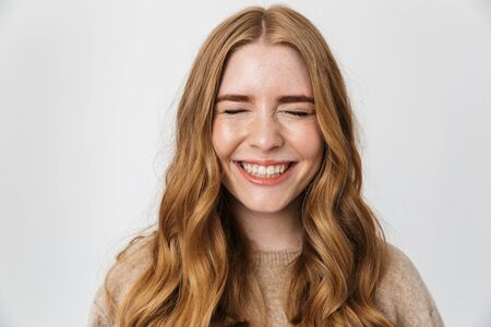 Close up of a beautiful cheerful young girl with long blond curly hair wearing sweater standing isolated over white background