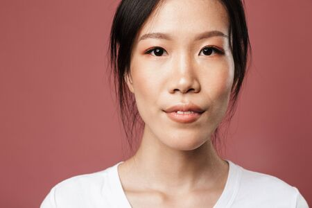 Portrait of beautiful asian woman dressed in basic wear smiling and looking at camera with lovely glance isolated over red background in studio