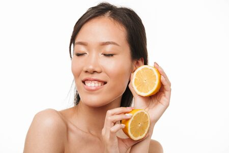 Image of a happy excited young beautiful asian woman posing isolated over white wall background holding lemon.