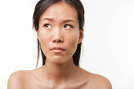 Image of a sad confused young beautiful asian woman posing isolated over white wall background.