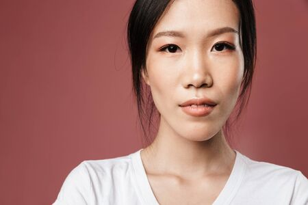 Portrait of young asian woman dressed in basic wear looking at camera with lovely glance isolated over red background in studio