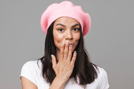 Photo closeup of shy pretty woman in basic t-shirt and beret looking at camera and covering her mouth with hand isolated over gray background