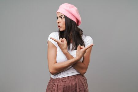 Attractive confused young brunette woman wearing beret standing isolated over gray background, presenting copy space