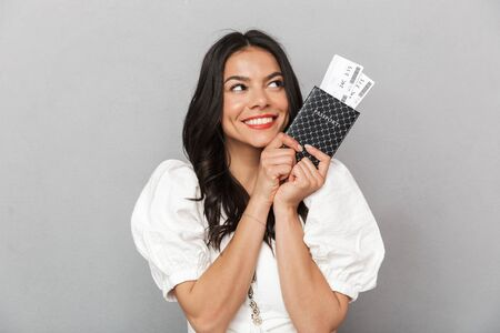 Portrait of a beautiful young brunette woman wearing summer outfit standing isolated over gray background, showing passpport with flight tickets