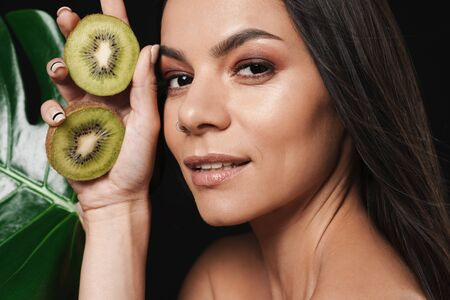 Beauty portrait of an attractive young topless woman with long brunette hair isolated over black background, posing with sliced kiwi fruit