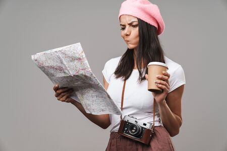 Image closeup of perplexed young tourist woman with retro vintage camera and takeaway coffee thinking and looking at paper map isolated over gray background