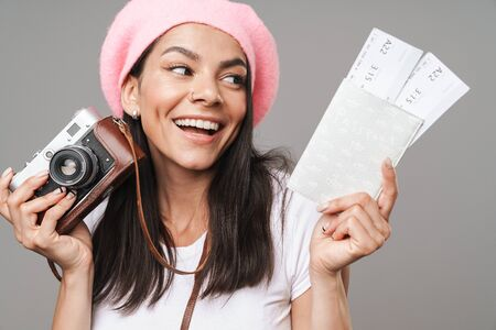 Photo closeup of seductive pretty tourist woman in beret smiling while holding retro camera and travel tickets isolated over gray background Zdjęcie Seryjne