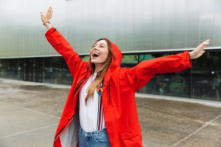 Image of beautiful excited emotional young happy pretty woman in raincoat posing outdoors.