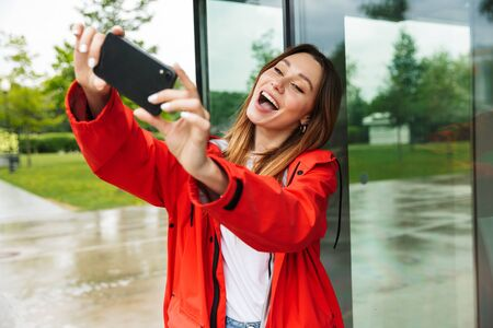 Cheerful attractive young girl wearing raincoat spending lovely time outdoors, taking a selfie Standard-Bild - 128675186