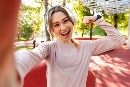 Image of a beautiful cheerful young fitness sports woman posing outdoors in park listening music with earphones take selfie by camera showing biceps.
