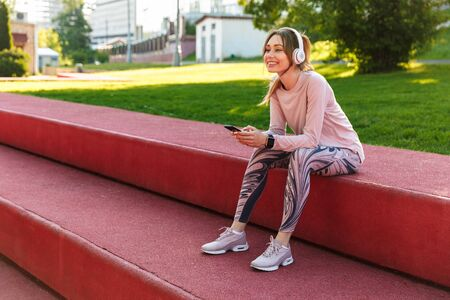 Image of a beautiful young fitness sports woman posing outdoors in park listening music with earphones using mobile phone.